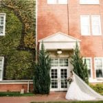 Bride stands in front of brick and ivey wall for her Uptown Charlotte North Carolina Wedding coordinated by Magnificent Moments Weddings