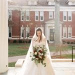 Bride poses with large hand tied bridal bouquet designed by Jimmy Blooms
