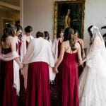 Bride pray with bridesmaids before her uptown wedding ceremony at Queen's University Belk Chapel