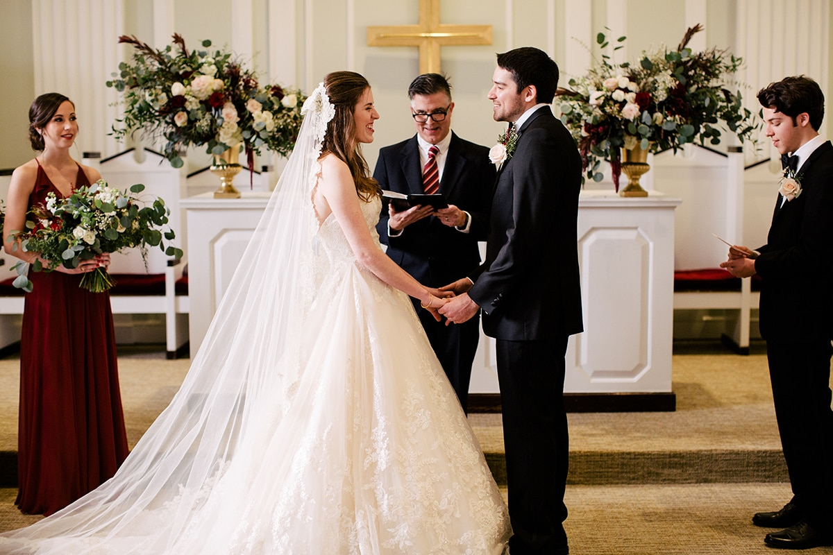 Bride and groom exchange vows at Queen's University Belk Chapel captured by Cameron Faye Photography