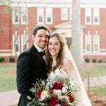 Bride and groom post for stunning portrait, bride holding stunning bridal bouquet with deep red flowers by Jimmy Blooms