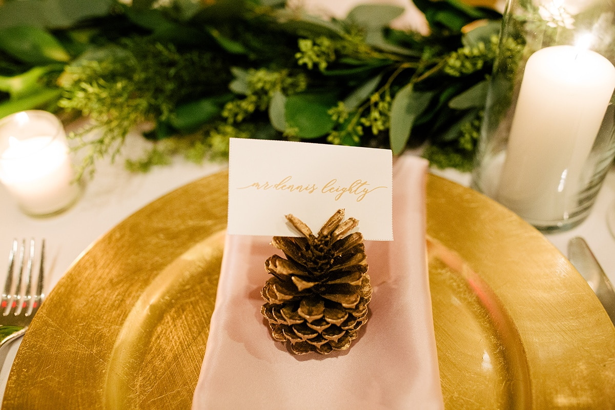 Adorable gold pinecone serves as place card holder at a Uptown Charlotte Mint Museum Wedding