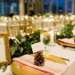 Beautiful table setting with gold chargers and blush napkins, gold pine cones serve as place card holders accented by stunning green garland created by Jimmy Blooms