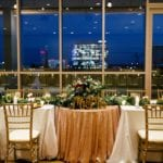 Bridal party head table with amazing gold chiavari chairs set off by uptown skyline at a Magnificent Moments Weddings coordinated event
