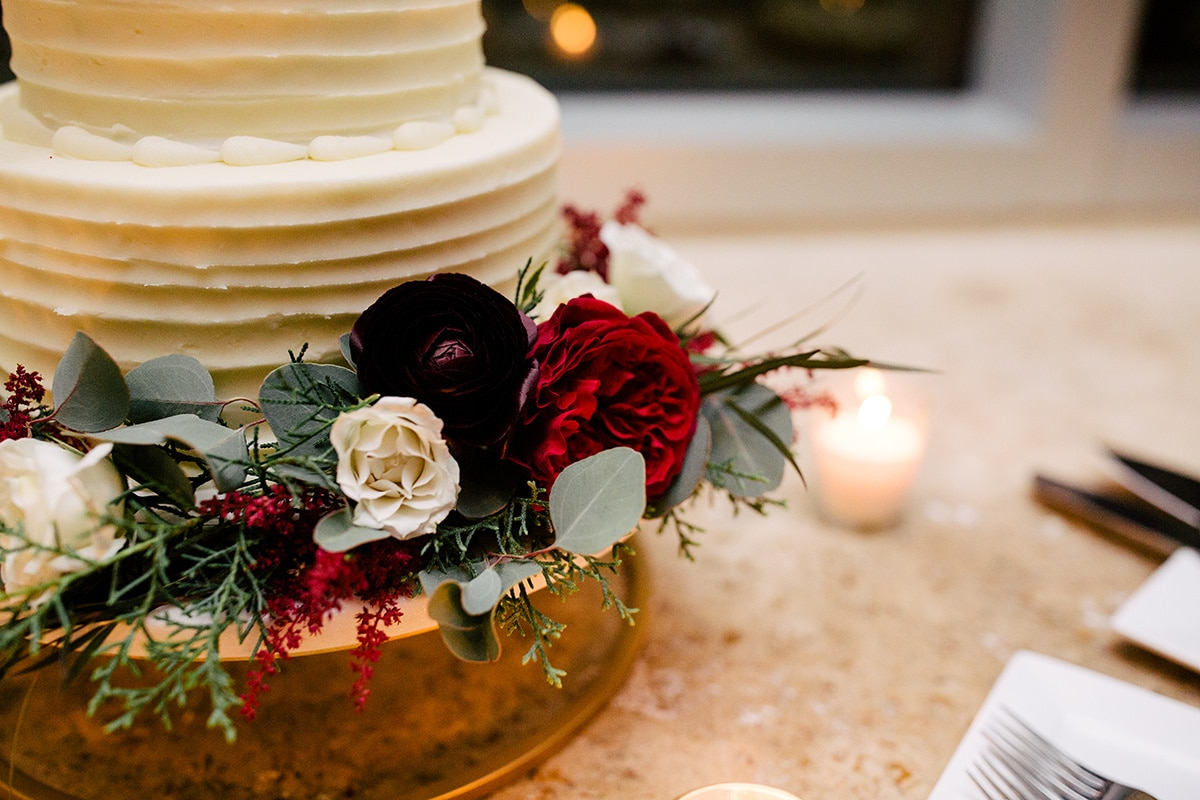 Deep red winter flowers accent simple white cake by Edible Art Cake Shop and captured by Cameron Faye Photography