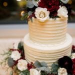 Two tier white cake by Edible Art Cake Shop is beautiful with blush and red flowers as a topper and bottom tier ring