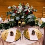 Sweetheart table for bride and groom set with glittering pink linen and gold chargers accented by blush napkins and pinkconeplace holders, amazing floral centerpiece and garland created by Jimmy Blooms