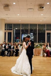 Bride and groom embrace during first dance at wedding coordinated by Magnificent Moments Weddings
