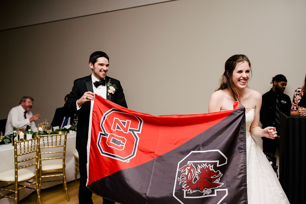 Bride and groom show of college rivalry for their uptown wedding captured by Cameron Faye Photography