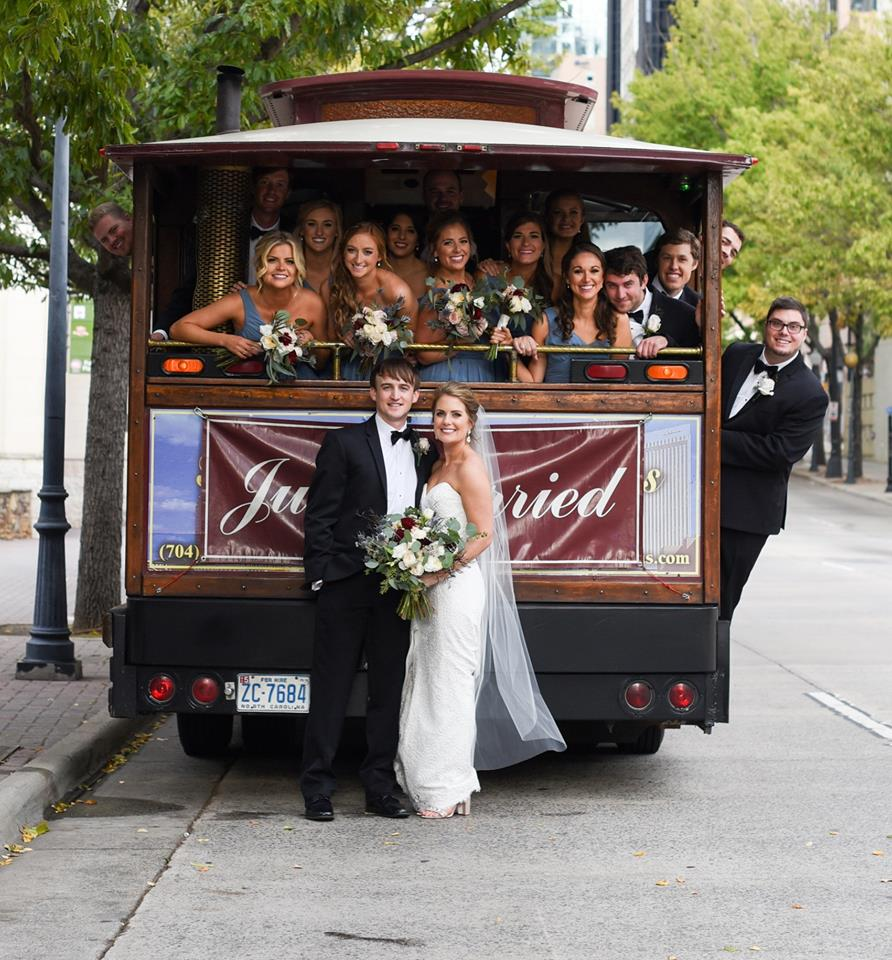 Bride and groom with bridal party posing behind vintage trolley rented from Sunway rentals, uptown wedding party photos captured by George Street Photography