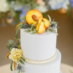 Natural peach wedding cake topper pulls together a southern reception as it sits on a bed of simple greenery by Sky's the Limit Cakes