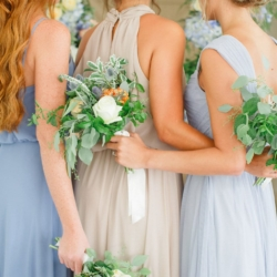 Bridesmaids hold hand tied bouquets featured white roses and peach and blue toned accent flowers with greenery from Jimmy Blooms