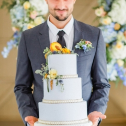 Simple three tier white cake from Sky's the Limit Cakes held by a southern groom