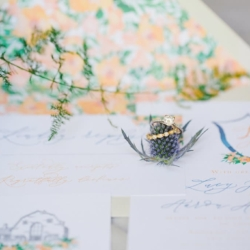 Bridal ring detail shot above peach and blue wedding invitation suite captured by Julia Fay Photography