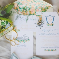 Wedding stationary shows off a suite of peach and blue inspired design with soft calligraphy by Ocean and Coral Creative with peach flowers and detailed drawing of The Dairy Barn wedding venue