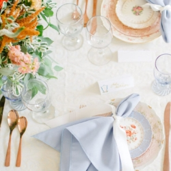 Peach and blue wedding tablescape with vintage china rose gold silverware and soft white lace linens