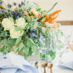Peach and blue toned centerpiece with white roses and greenery accents created by Jimmy Blooms