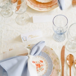 Elegant peach and blue table setting with soft blue napkins tied with a white ribbon show off a southern styled event at The Dairy Barn in Fort Mill South Carolina
