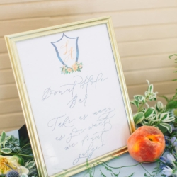Wedding crest displayed atop a calligraphy created bar sign detailing signature wedding cocktails for a vintage southern wedding styled by Magnificent Moments Weddings