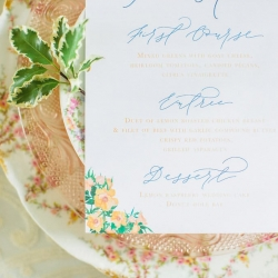 Blue and peach flowers make a dinner menu card pop overtop of vintage peach floral china at a southern wedding at Fort Mill's The Dairy Barn