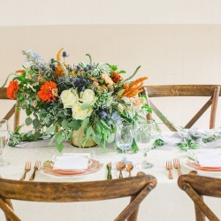 Peach and blue toned wedding tablescape with gorgeous white rose centerpiece accented with peach and blue toned florals by Jimmy Blooms