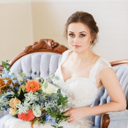 Bride on light blue sette rented from Evermore Event Company with stunning hand tied peach and blue bridal bouquet by Jimmy Blooms