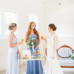 Bridal party enjoying peach Bellini cocktails at a southern peach and blue styled wedding