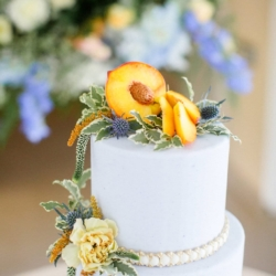 Simple white cake with pearl detail on each tier natural peach topper by Sky's the Limit Cakes
