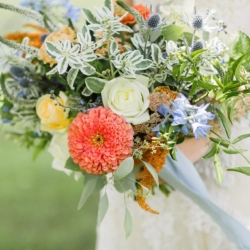 Hand tied bridal bouquet with peach and blue toned florals by Jimmy Blooms