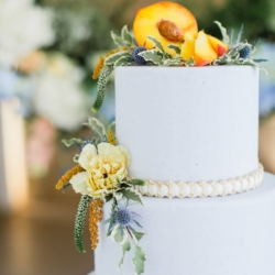 White cake with pearl detail. Has fresh peach as a cake topper nestled atop greenery photography by Julia Faye Photography