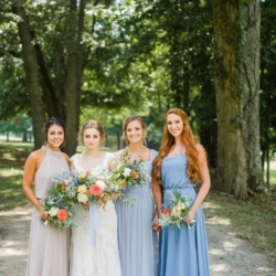 Soft blue bridesmaids dresses from Simpson Bridal with hand tied bouquets featuring blue and peach toned florals by Jimmy Blooms