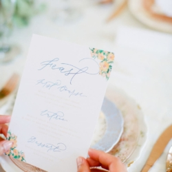 Blue and Peach menu card beautiful blue calligraphy by Ocean and Coral Calligraphy over top vintage blue and peach china