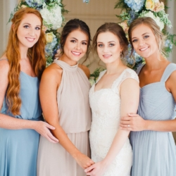 Bridal party in soft blue bridesmaids dresses pose in front of blue and peach hanging flower frame made by Jimmy Blooms