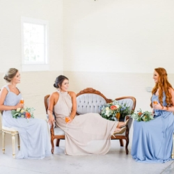 Blue bridesmaids dresses with vintage blue settee rented from Charlotte's Evermore Event Company, bridesmaids holding blue and peach hand tied bouquets by Jimmy Blooms