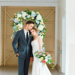 Hanging flower frame with blue and white hydrangeas behind a Charlotte bride holding beautiful hand tied bouquet by Jimmy Blooms