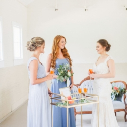 Bride with bridesmaids wearing light blue dresses from Simpson's Bridal enjoying cocktail hour of peach bellini's for a southern peach and blue toned wedding