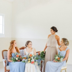 Bridal party portrait with bridesmaids in soft blue toned dresses holding peach and blue hand tied bouquets by Jimmy Blooms