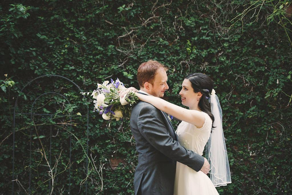 bride and groom portraits with a greenery wall backdrop