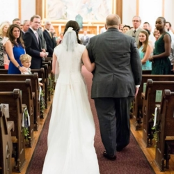 father of the bride and bride walking down the aisle at st peters catholic church in uptown charlotte