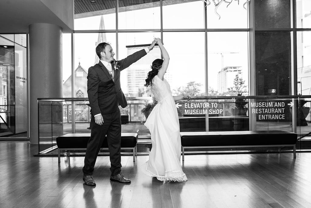 bride and groom practicing their first dance in the lobby at the Mint Museum Uptown