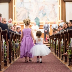 flower girls walking down the aisle at St. Peters Catholic Church in Charlotte