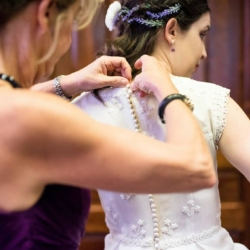 Mom helping button the bride into her dress