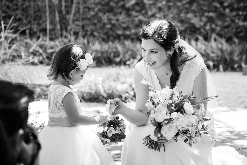 bride giving flowers to the flower girl