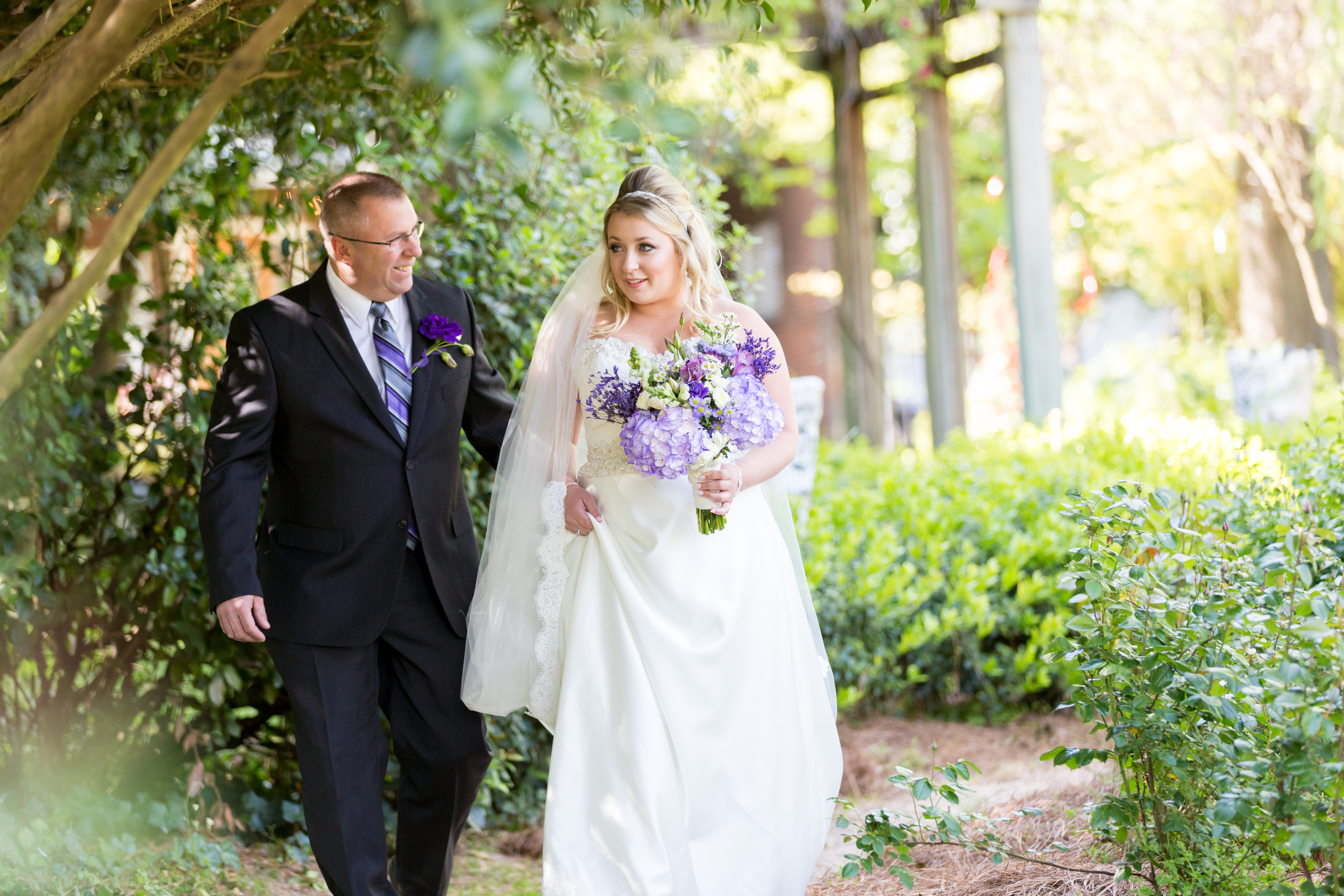 father of the bride walking with the bride down the aisle at McGill Rose Garden in Charlotte NC