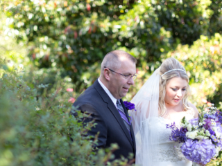 father of the bride walking with the bride at McGill Rose Garden in Charlotte NC