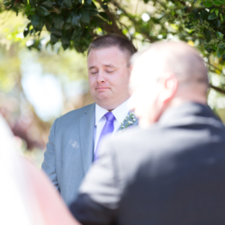 Groom tearing up seeing his bride walk down the aisle at McGill Rose Garden in Charlotte NC