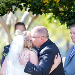 Father of the Bride kissing his daughter on the cheek at the end of the aisle