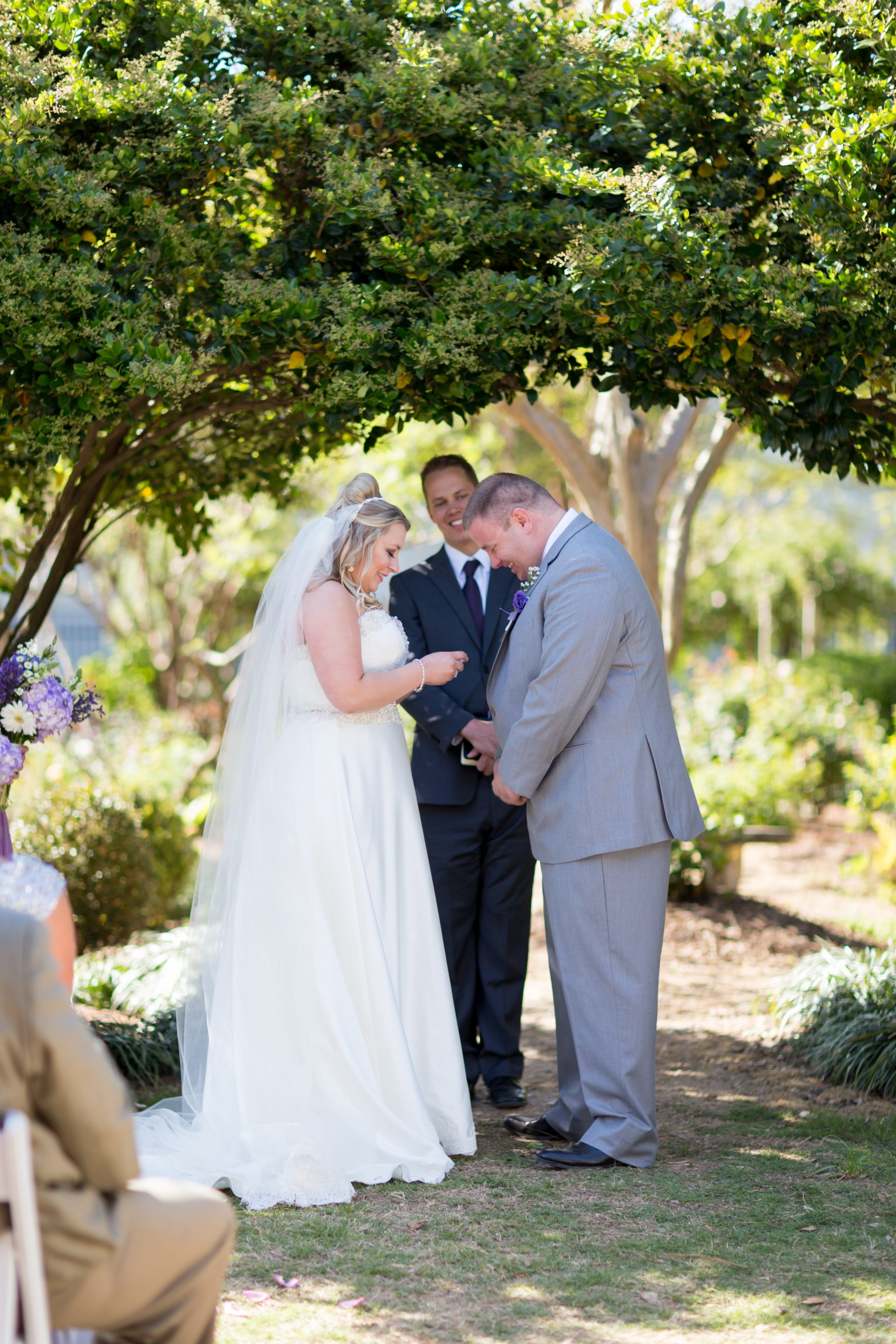 Exchanging vows during their wedding ceremony at McGill Rose Garden in Charlotte NC photo by Keith Marwitz Photography