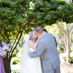 Kissing during their wedding ceremony at McGill Rose Garden in Charlotte NC photo by Keith Marwitz Photography