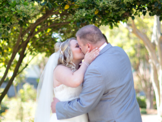 Kissing the bride during their wedding ceremony at McGill Rose Garden in Charlotte NC photo by Keith Marwitz Photography